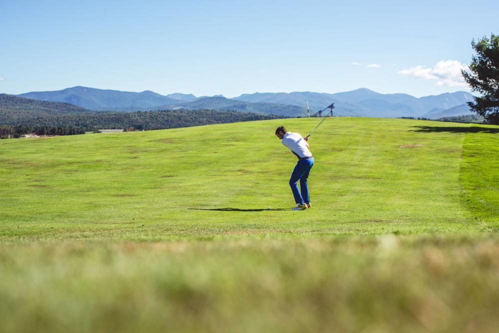 A man golfs on a green with mountains in the background.