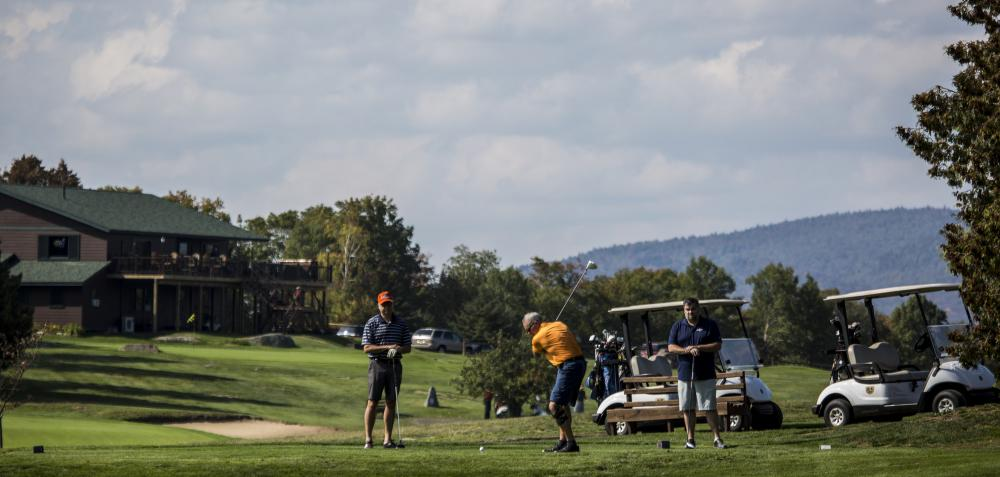 Three men golf with golf carts and clubhouse in the background.