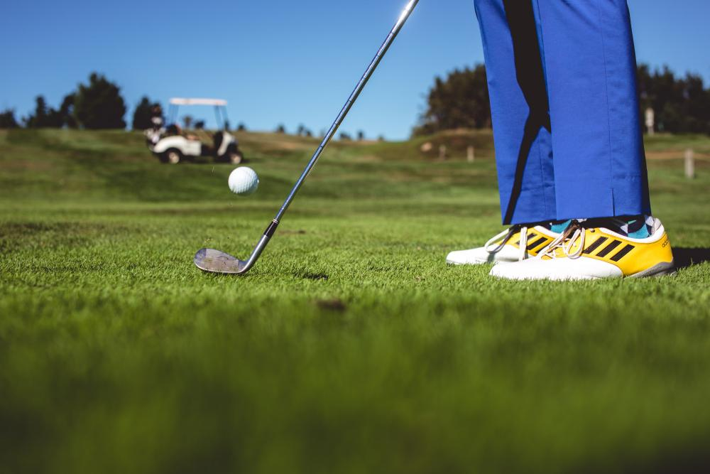 Close-up of a golfer's feet as he strikes the ball with cart in background.
