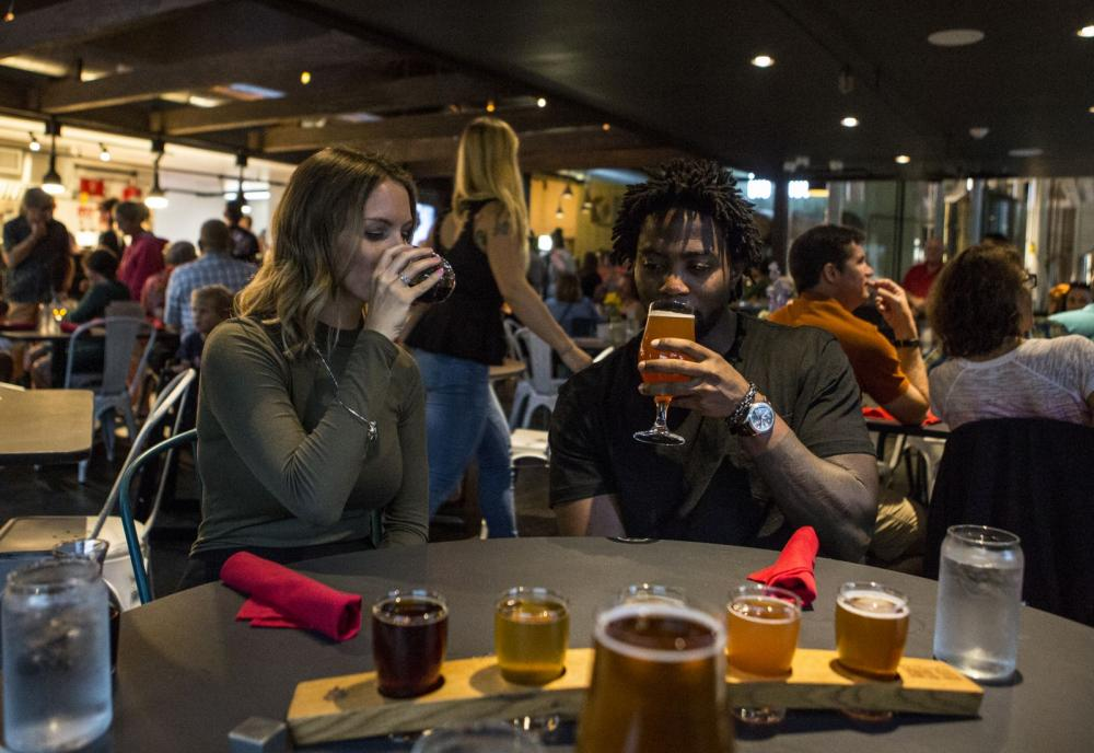 A man and woman sample beer in a busy Adirondack pub.