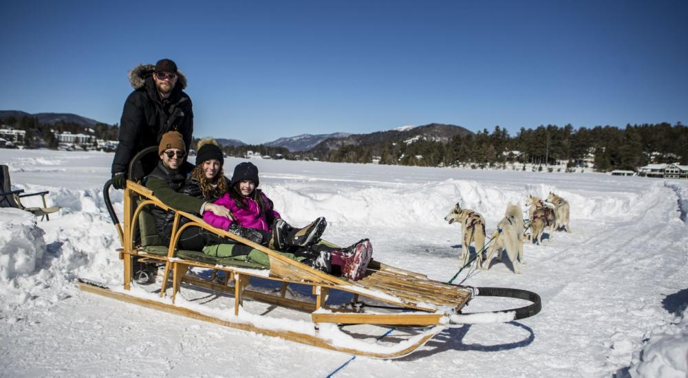 A family of three sits in a dog sled on snowy, frozen Mirror Lake.
