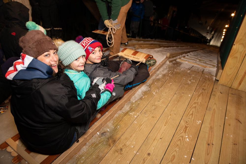 A woman and two children prepare to slide down the toboggan chute.