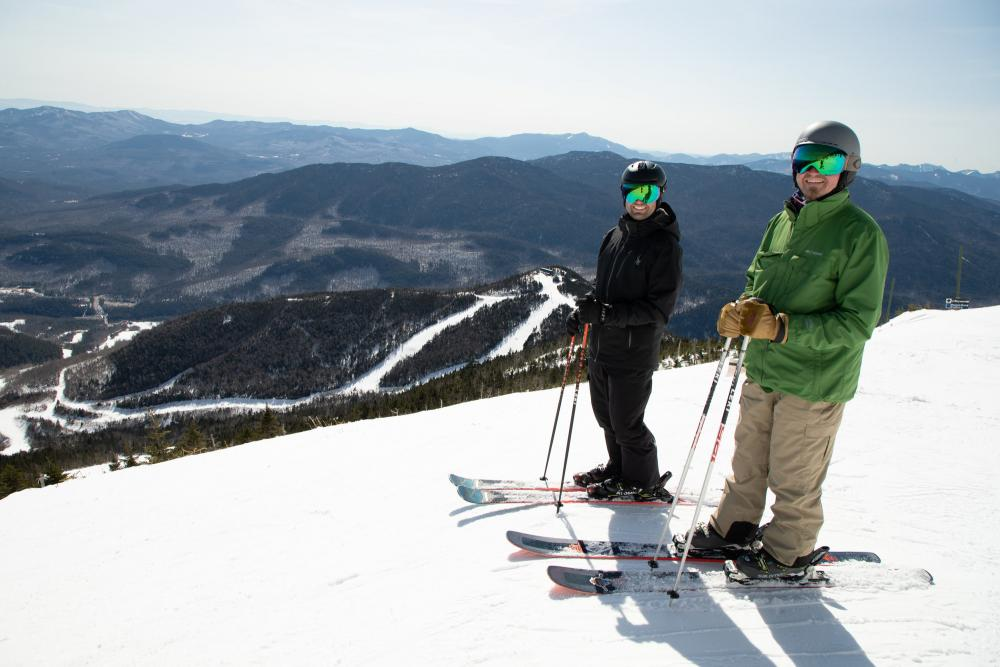 Two skiers pose on a snowy peak high above a mountain valley.