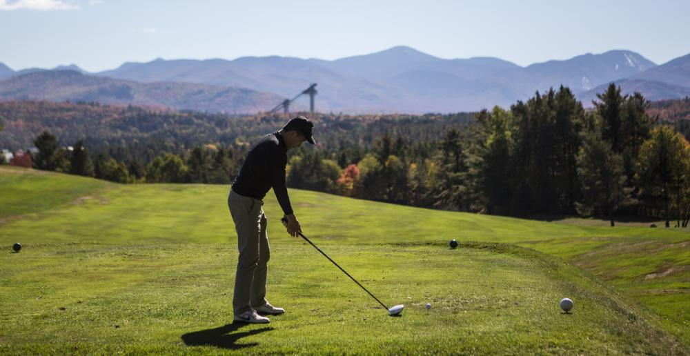 A golfer tees off with the Adirondack High Peaks and Olympic ski jumps in the background.