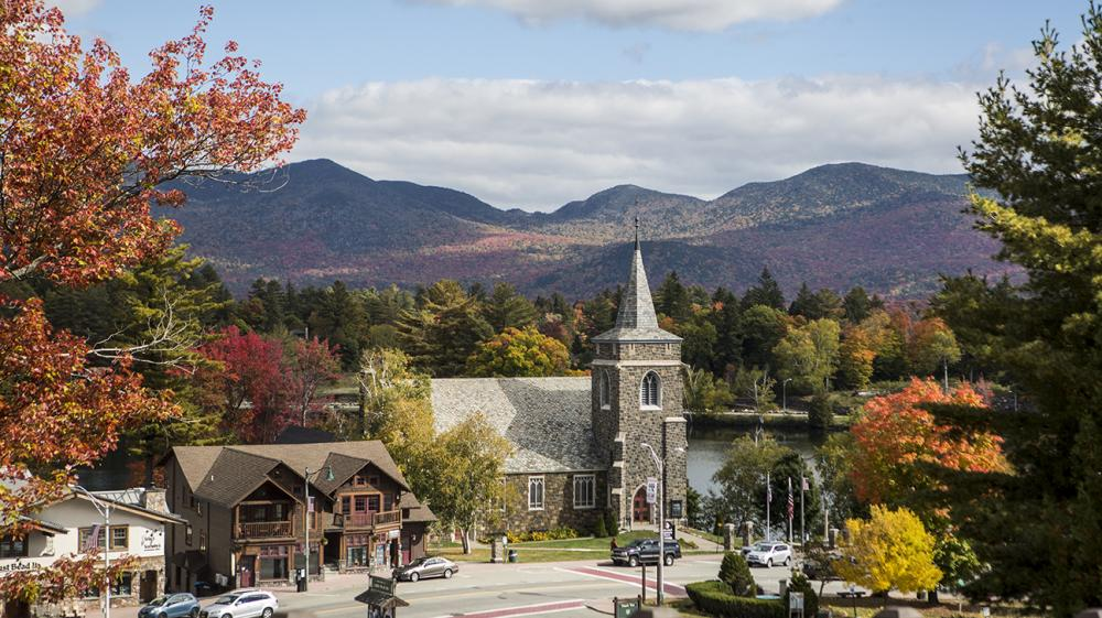 A scenic view of Mirror Lake and a local church amid fall foliage.