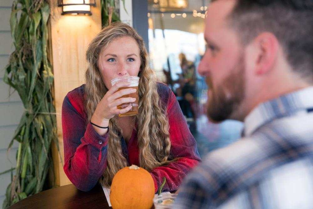 A young woman drinking a beer in Lake Placid in the fall.