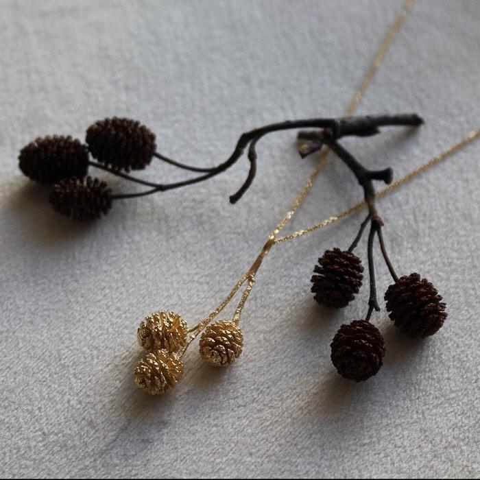 A delicate golden pinecone pendant, a sweet Adirondack souvenir.