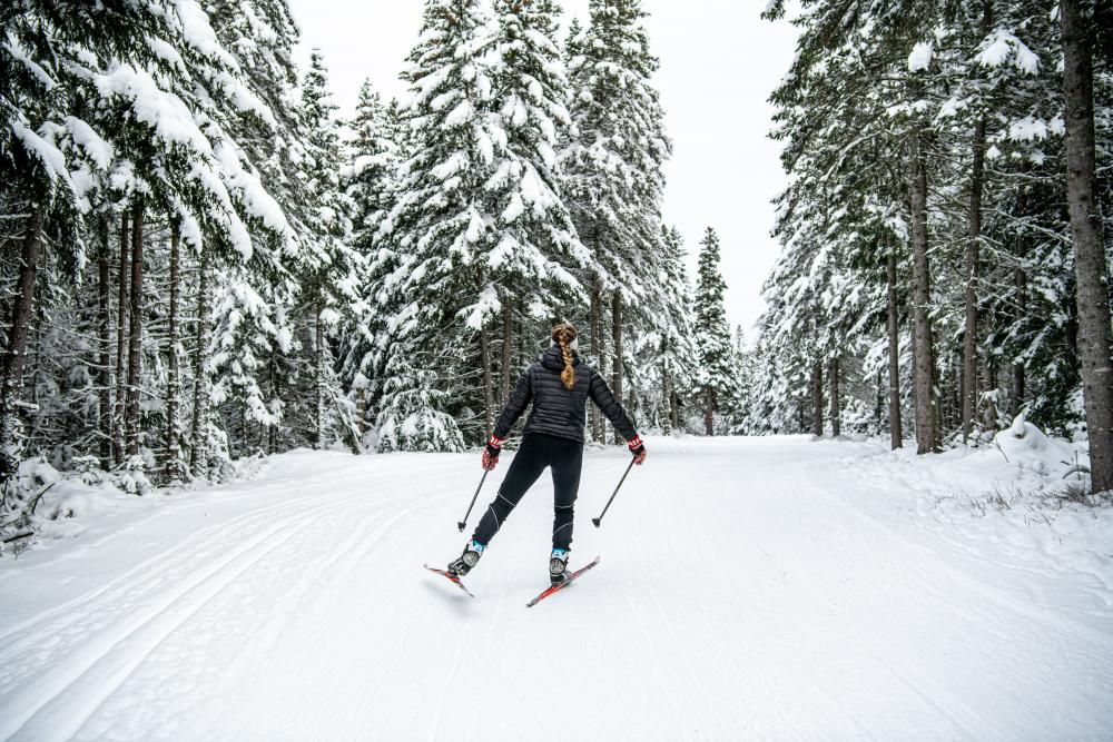 Woman cross-country skiing on snowy trail.