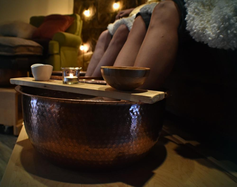 Two people sit with their feet in hammered copper bowls for a foot treatment.
