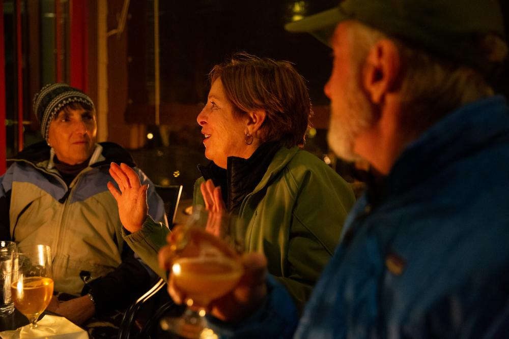 Two women and a man chat over a meal at an outdoor fire in winter.