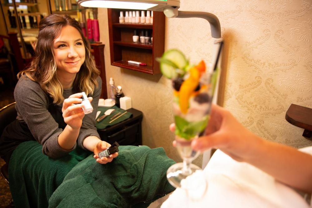A woman offers nail polish selections to a spa client enjoying a fruit dessert.
