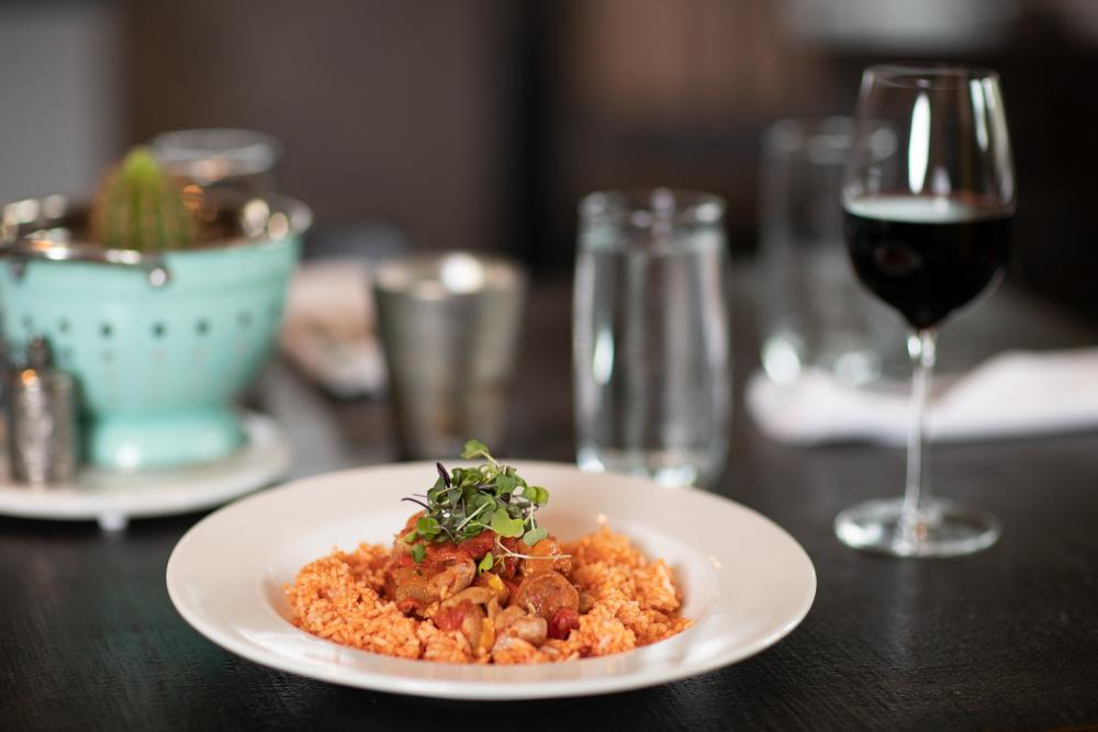 A plate of rice and jambalaya and glass of wine on a modern dining table.