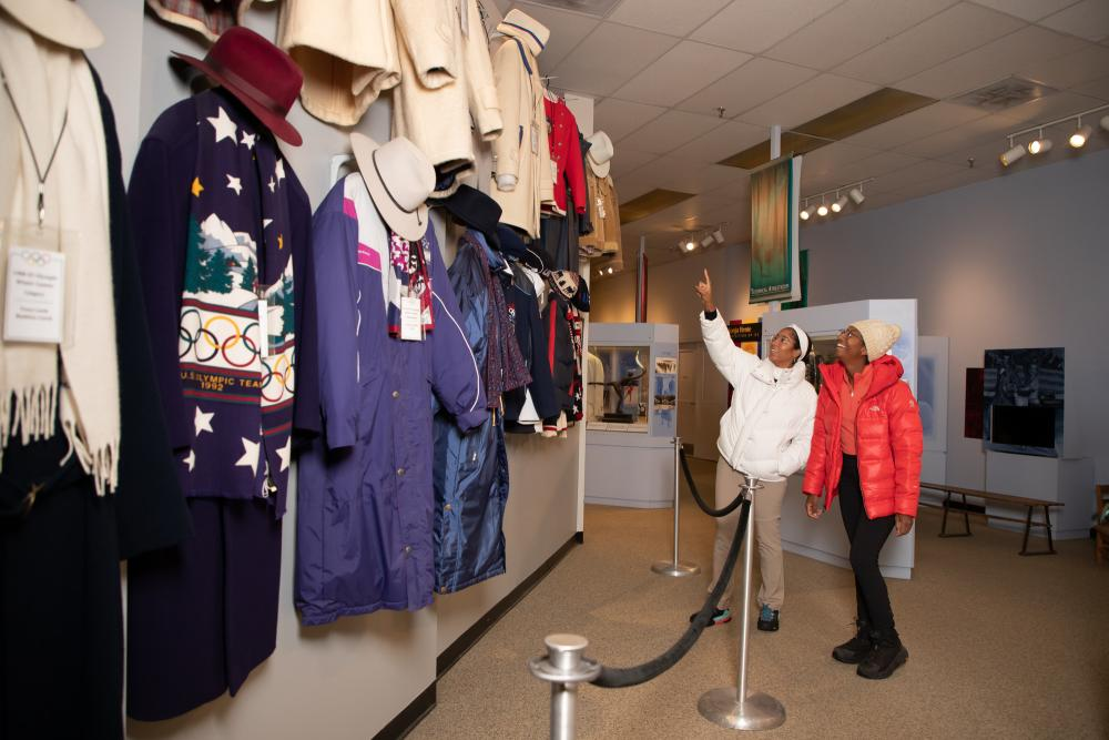 Two women admire historic uniforms at the Lake Placid Olympic Museum.