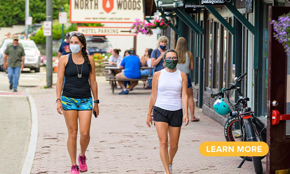 Two women stroll Main Street in masks and summer clothing.