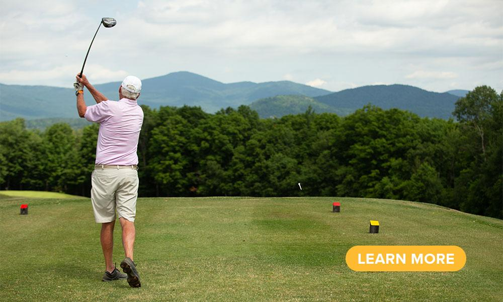 A golfer tees off toward the Adirondack Mountains.