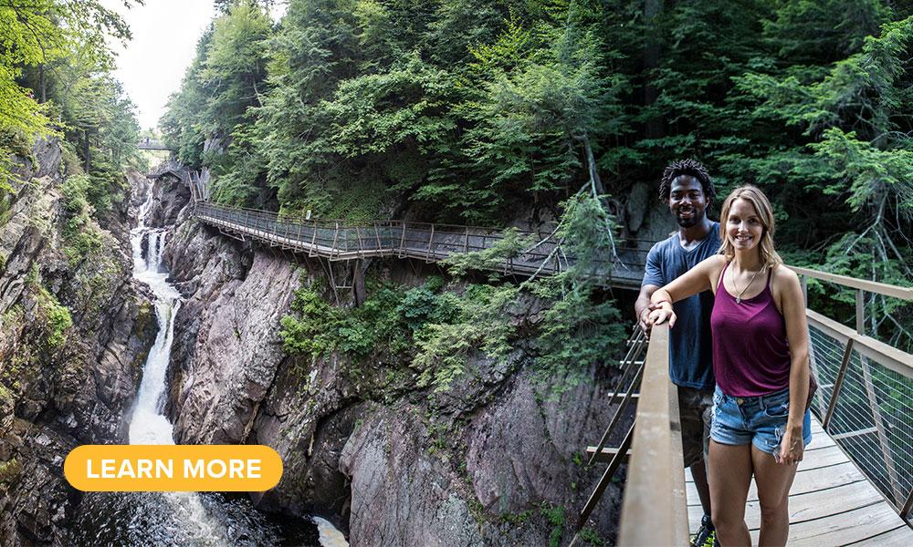 A couple poses on a footbridge crossing over High Falls Gorge.