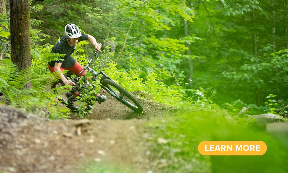 A mountain biker makes a turn on a wooded trail.