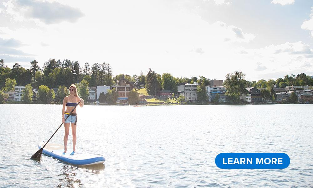 A woman paddles a SUP on Mirror Lake with Main Street in the background.