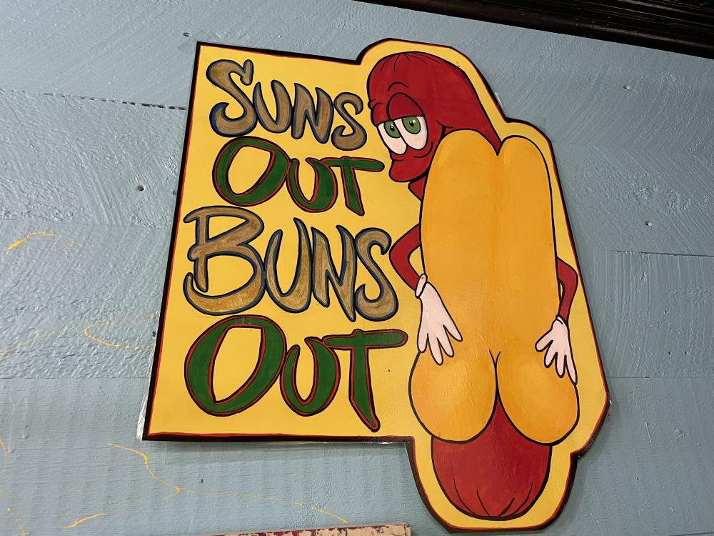"A vivid sign of a hot dog reads, ""Sun's out, buns out!"""