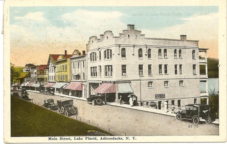 Vintage postcard of a row of buildings in Lake Placid, with early autos on the street. Image courtesy Lake Placid Public Library.