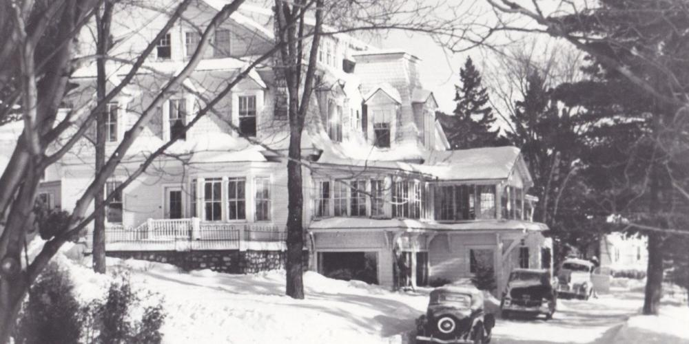 Vintage black and white photograph of the original Mirror Lake Inn, with early automobiles parked on the drive. Image courtesy Mirror Lake Inn.