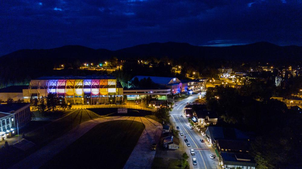 The Lake Placid Olympic Center buildings lit up at night.