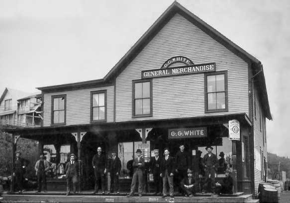 An antique black and white photograph of the general store in Newman, with men standing on the porch.