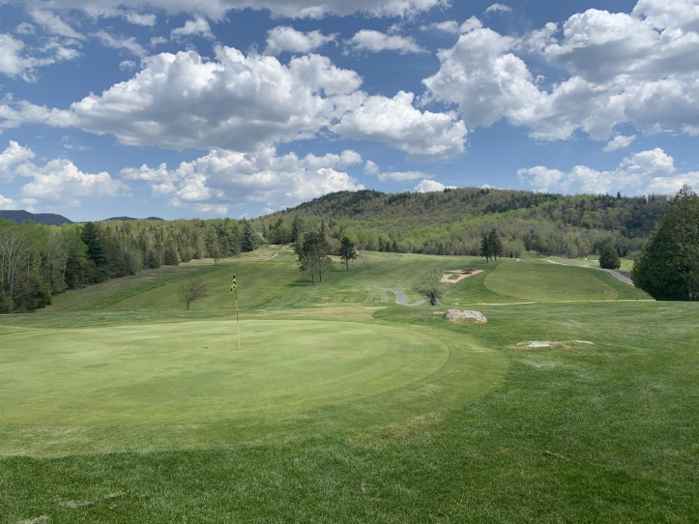 The #9 hole and the #8 green at Craig Wood Golf Club, with low mountains in the background.