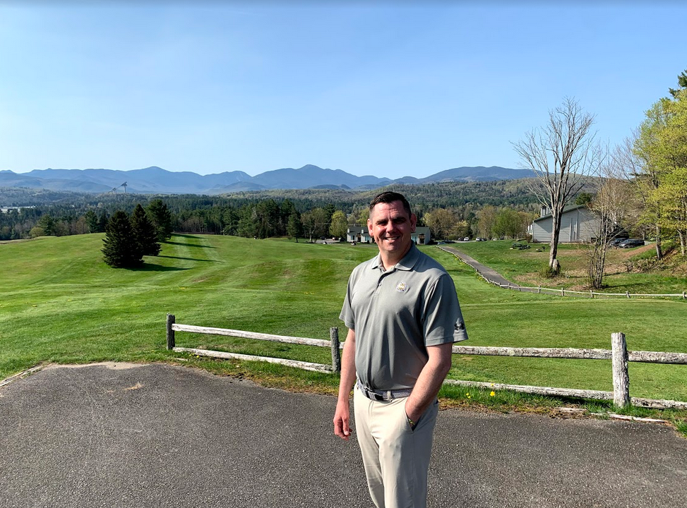 Lake Placid Club golf pro Jim Beauregard poses with the course and its Adirondack views behind him.