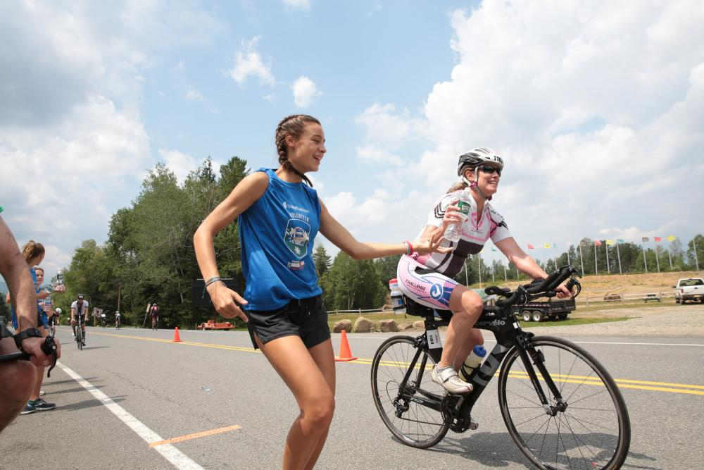 A volunteer hands off a bottle of water to a cyclist during the Ironman triathlon