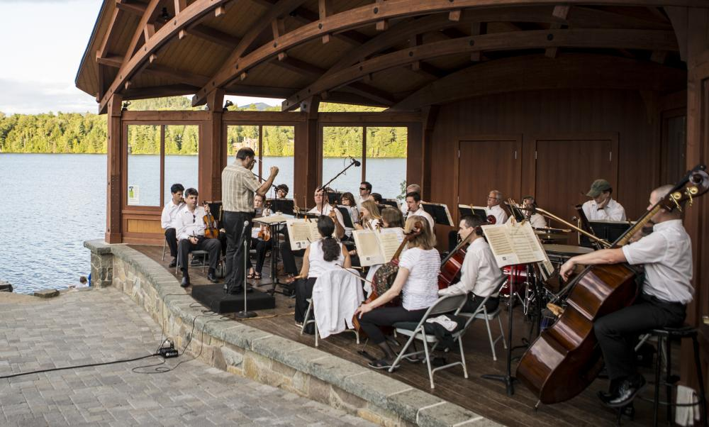 A sinfonietta performs on stage in front of Mirror Lake