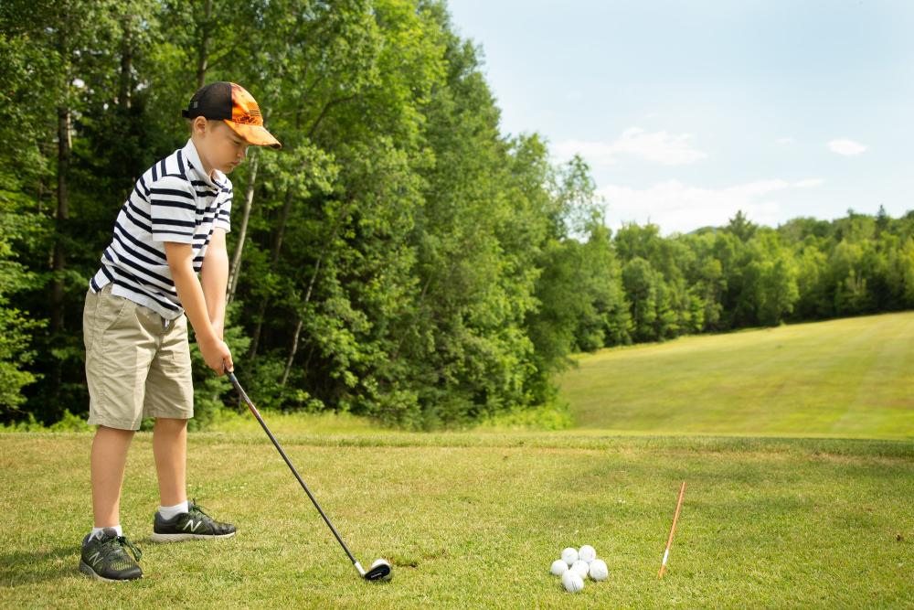 A young boy prepares to tee off on a golf green, with bright green trees along the fairway.