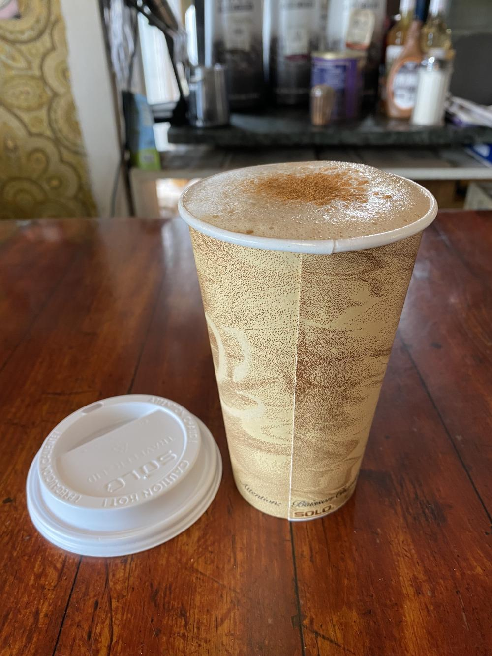 A foamy coffee drink on a wooden counter.