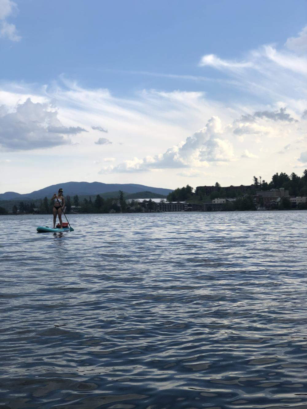 A woman paddles a SUP on a lake with mountains and trees in the background.