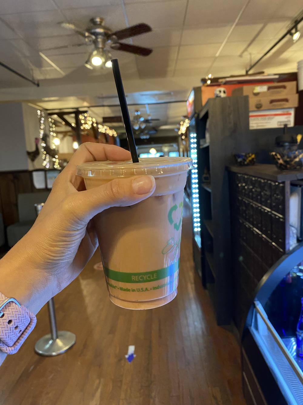 A womans hand holds up an iced coffee drink in a shop.