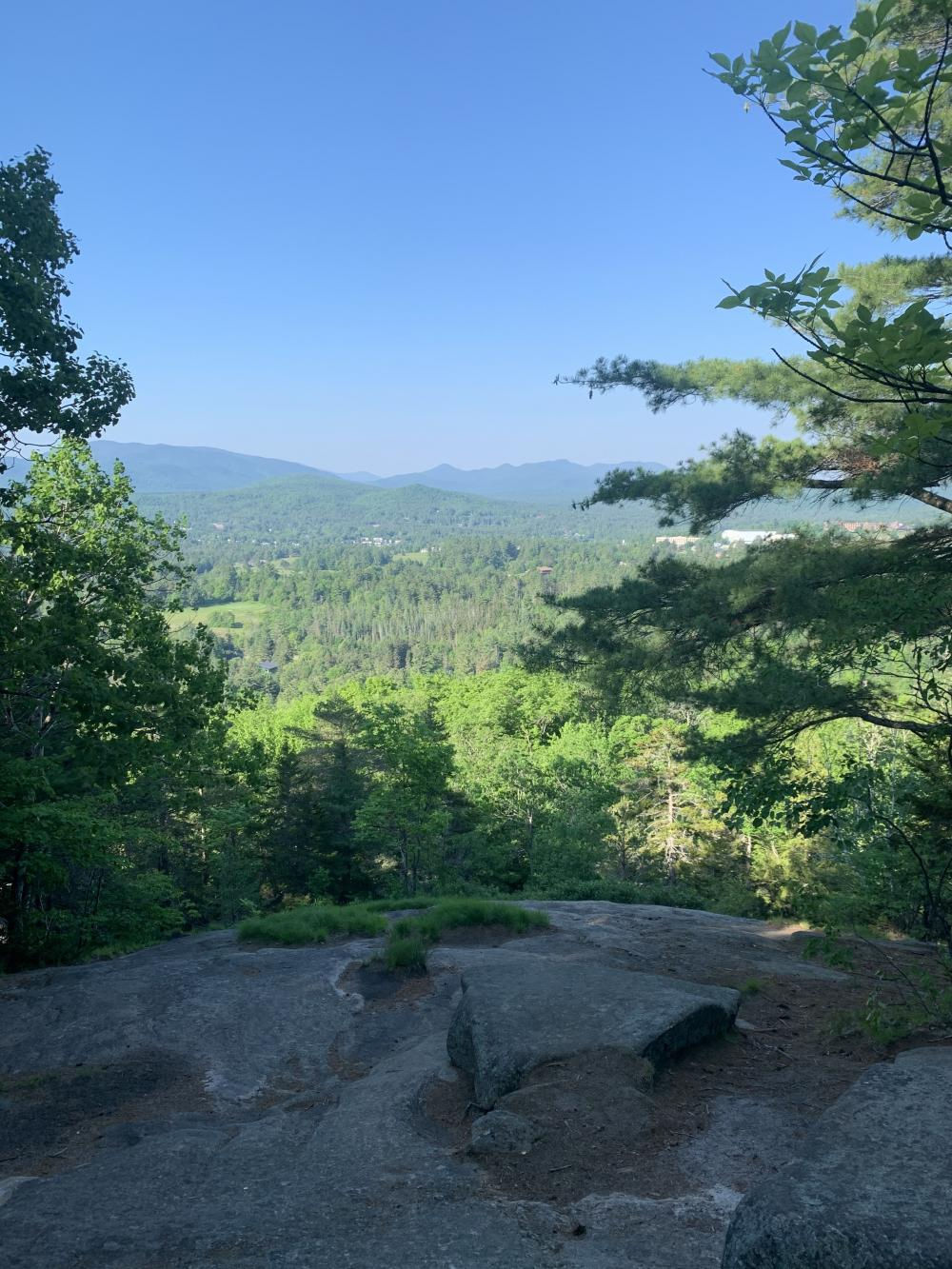 A rocky ledge offers a view of mountains and forest.