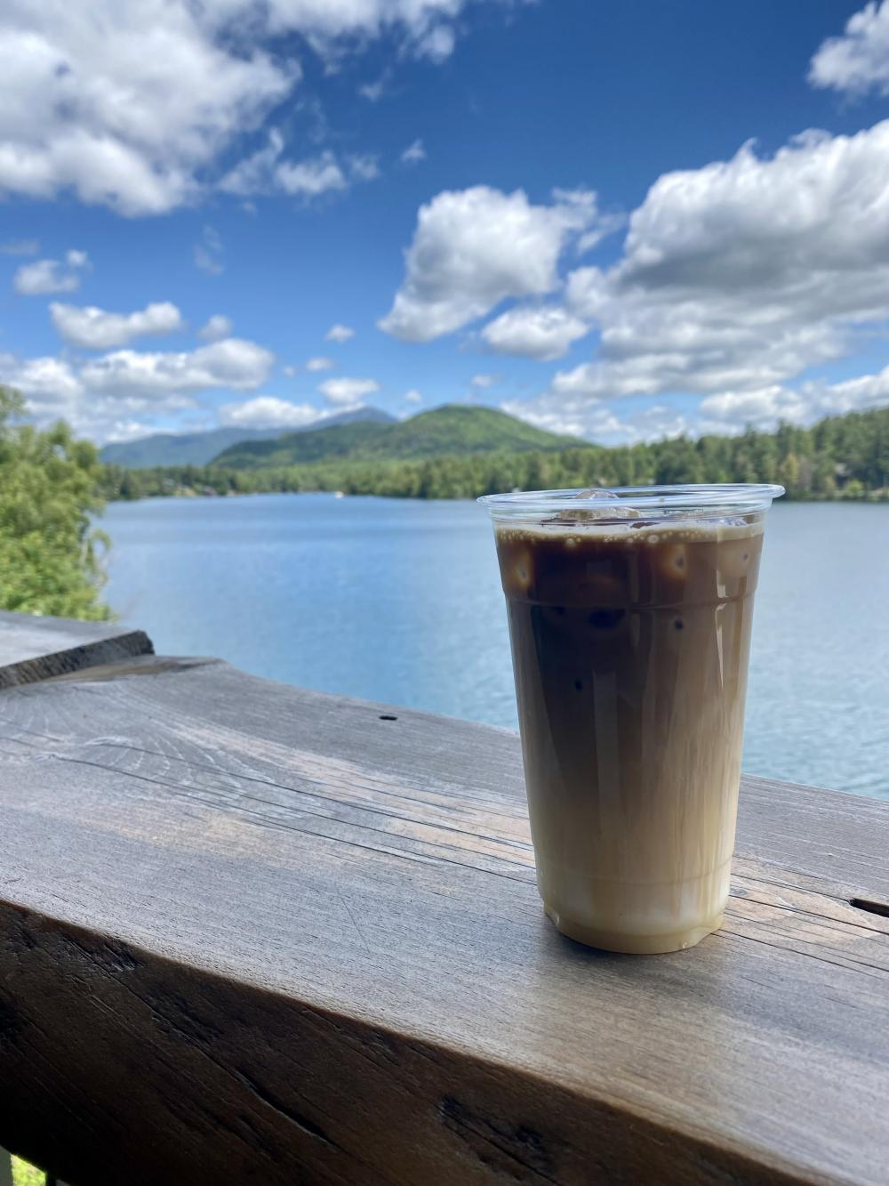 A cold coffee sits on a railing overlooking a sunny lake and mountains.