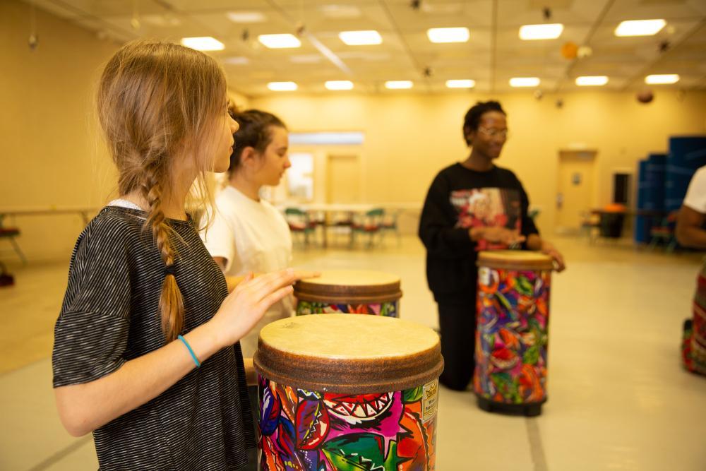 Three people in a bongo drum workshop.