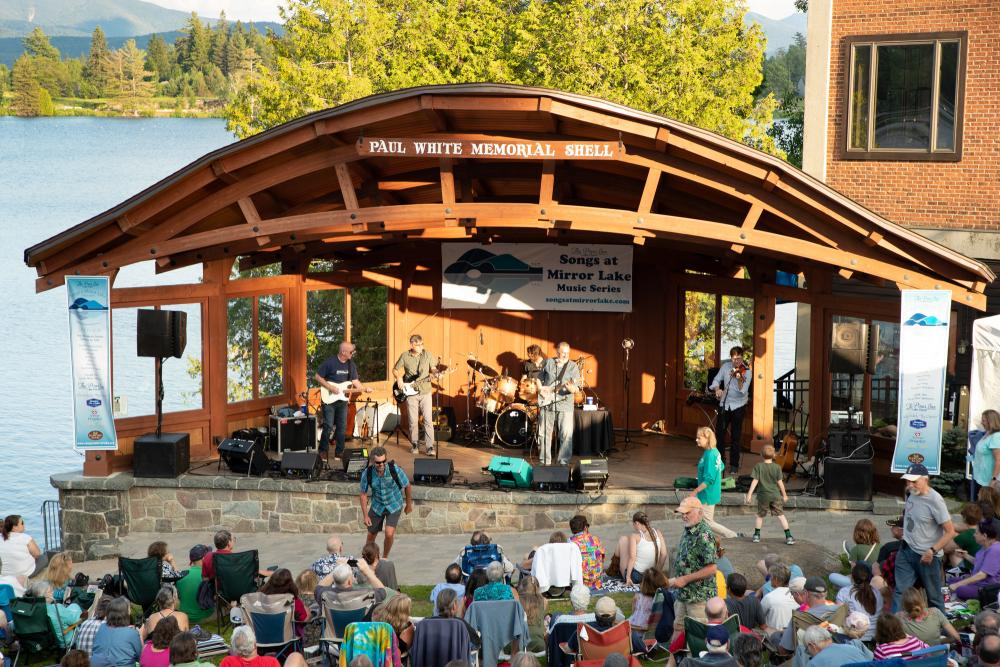 A band of four men plays in the bandshell next to Mirror Lake with an audience.