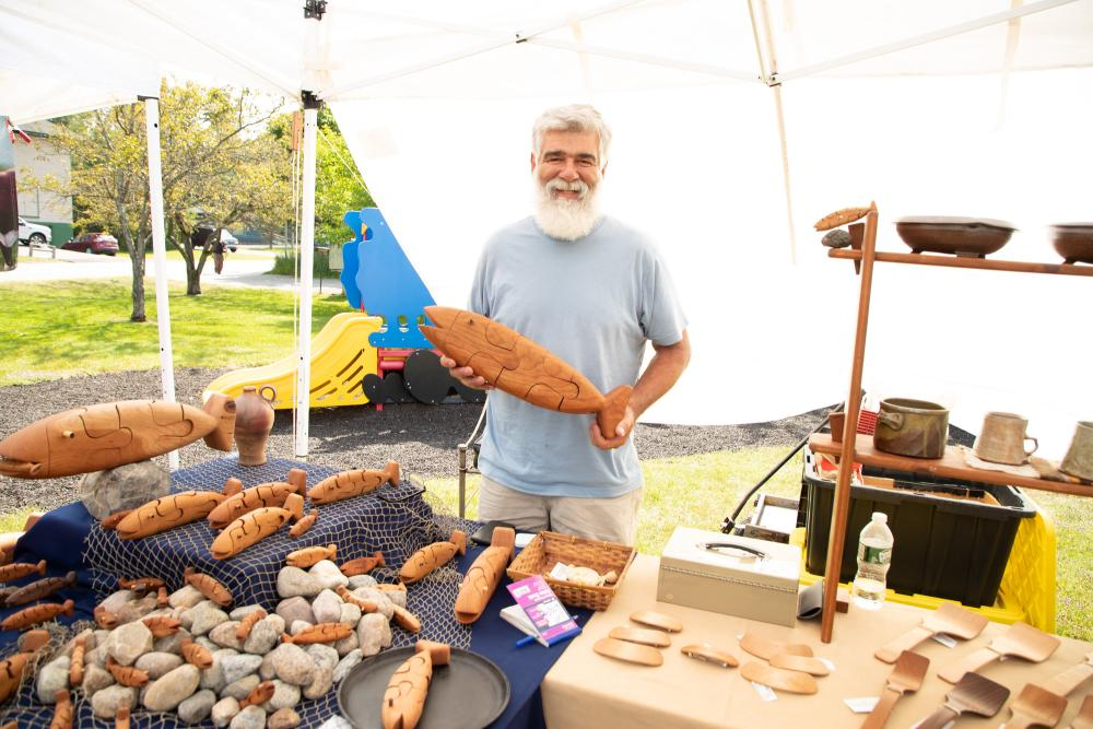 A local craftsman holds up a wooden fish at the farmers market.