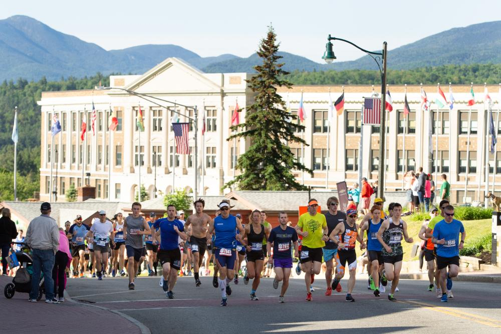 Runners race down a road as spectators look on.