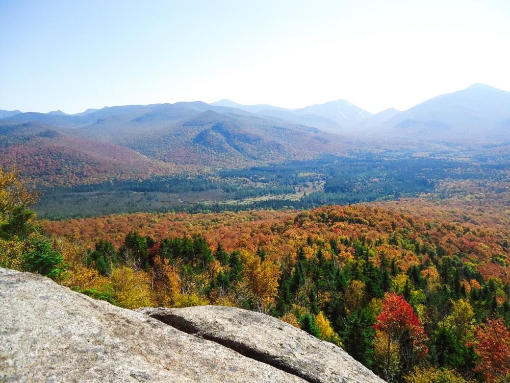 Fall view from the summit of Mount Van Hoevenberg. The High Peaks are covered in vibrant, colorful foliage.