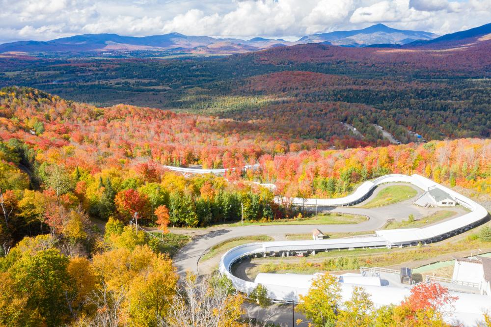 An aerial view of the bobsled track against a sea of colorful fall foliage.
