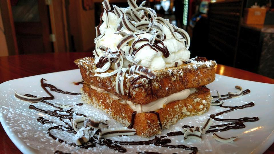 Two pieces of French toast with creamy filling and topped with a big mound of frosting and chocolate curls.