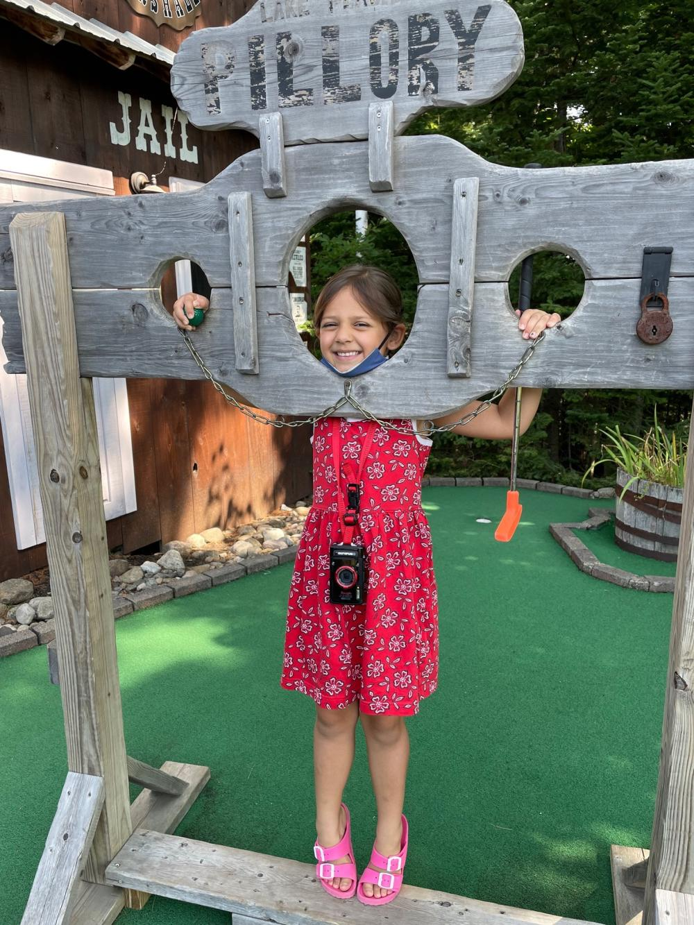 A small girl in a red dress poses in a wooden pillory on a mini golf course