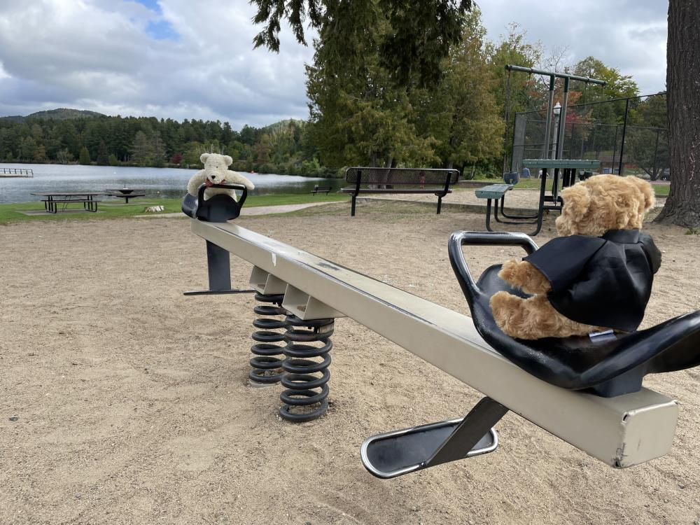 Two teddy bears sit on a teeter totter on a playground with a lake in the background.