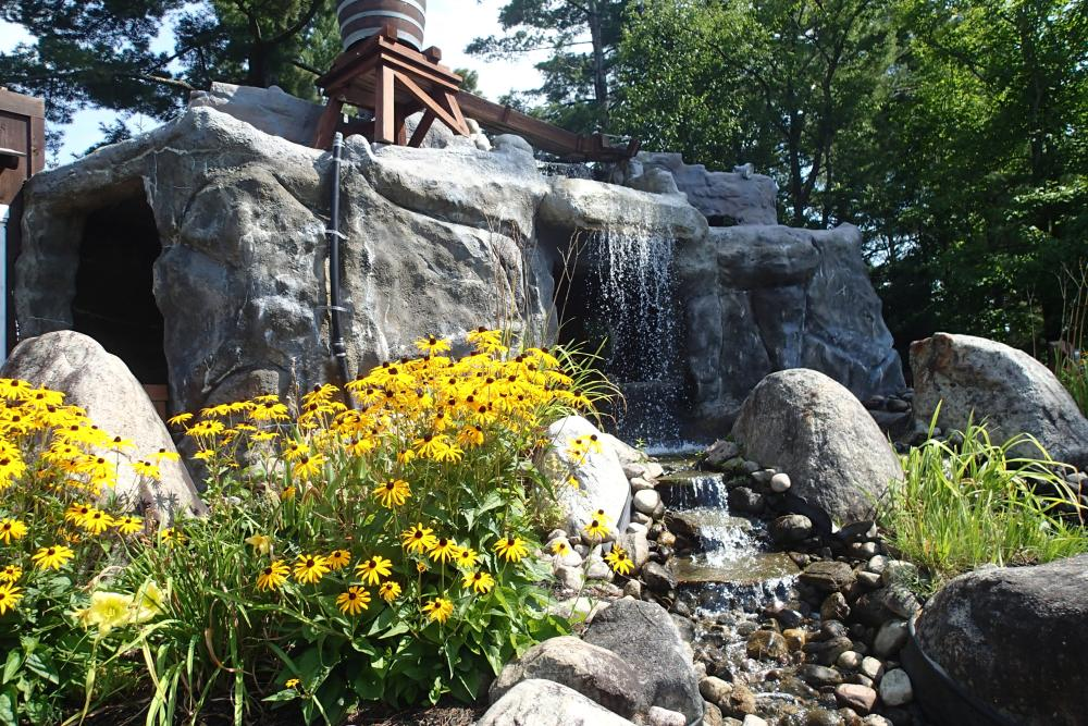 Black-eyed susan flowers in front of a rocky waterfall feature on a mini golf course.
