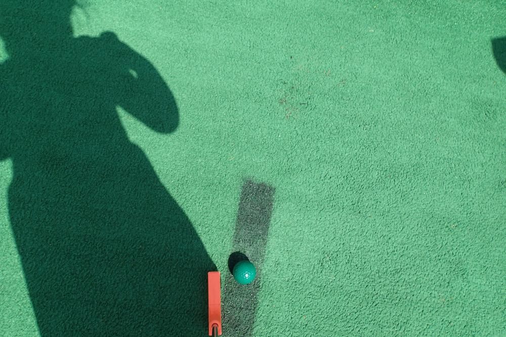An image of artificial turf on a mini golf course, with a putter, golf ball, and the shadow of a little girl.