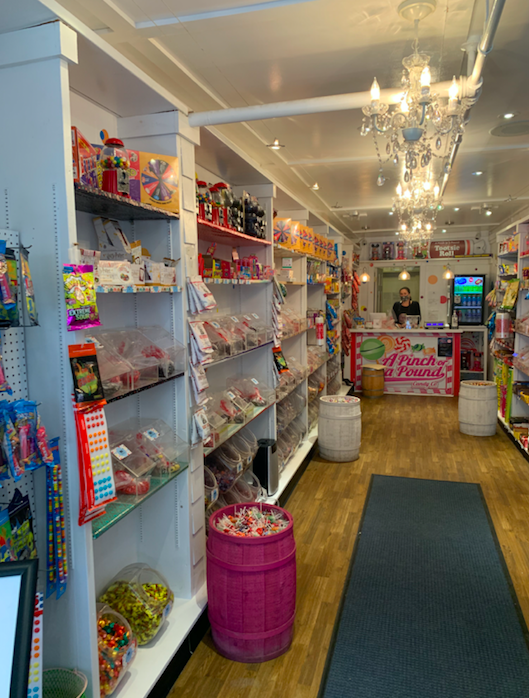 A white shop with chandeliers and shelves filled with brightly colored candy.